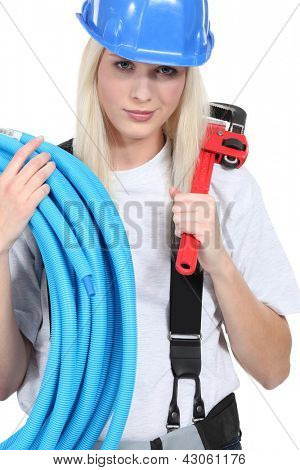 Tradeswoman holding corrugated tubing and a pipe wrench