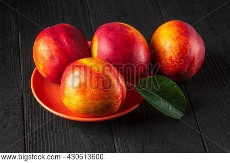 Red Ripe Nectarine Hybrids In Their Ripening Season Lie On Orange Plate Or On A Dark Vintage Table