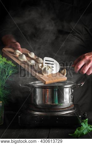 Chef Cooks Dumplings In A Saucepan In The Restaurant Kitchen. Close-up Of The Hands Of Cook During W