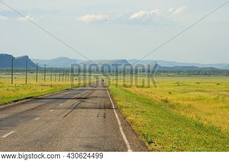 A Two-lane Asphalt Straight Road Runs Along The Power Line Through The Picturesque Steppe To The Mee