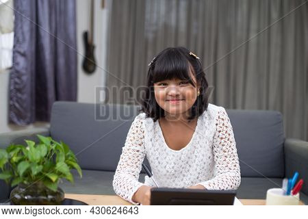 10 Years Old Southeast Asian Child Learning Distantly From Home. Online Education Using Tablet In Ne