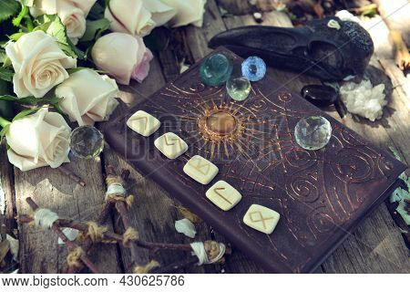 Still Life With Magic Witch Book, Runes, Crystal And Roses On Wooden Table.  Esoteric, Gothic And Oc