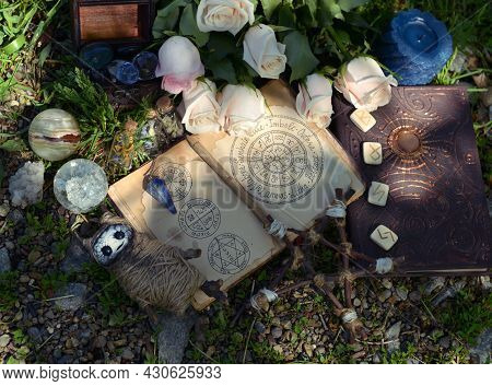 Wicca Ritual With Open Witch Diary, Pentagram And Voodoo Doll On The Grass. Esoteric, Gothic And Occ