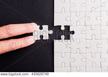 Top View Flat Lay Of Hand-holding Last Piece White Paper Jigsaw Puzzle Game Last Pieces Put To Place