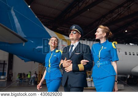 Happy Pilot In Uniform And Aviator Sunglasses Walking Together With Two Air Stewardesses In Blue Uni