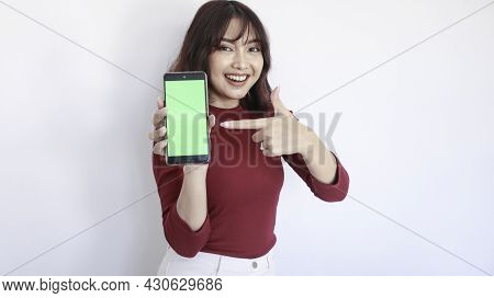 Happy Asian Beautiful Girl Point On Green Screen Phone In White Background