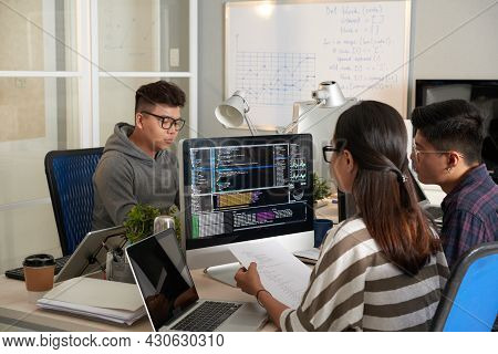 Young Woman Checking Programming Code On Computer Screen And Comparing With Code On Printed Document