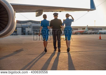 Full Length Shot Of Professional Pilot Walking Together With Two Female Flight Attendants In Blue Un