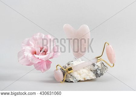 Crystal Rose Quartz Facial Roller And Massage Tool Jade Gua Sha On Stones And Natural Pink Flower On