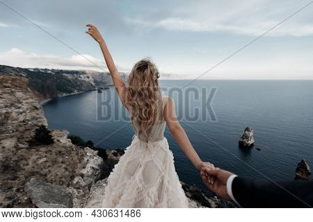 A Beautiful Blonde Bride In A Light Chiffon Wedding Dress Poses While Standing On A High Steep Bank