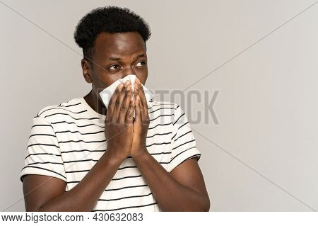 Sick African Man Blowing Nose In White Napkin. Young Guy Sneeze, Has Cold Or Flu. Studio Portrait Of