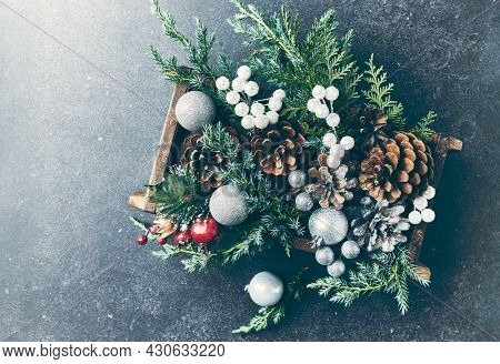 Pine cones, evergreen and Christmas balls in a rustic wooden box. Christmas decoration. Black background