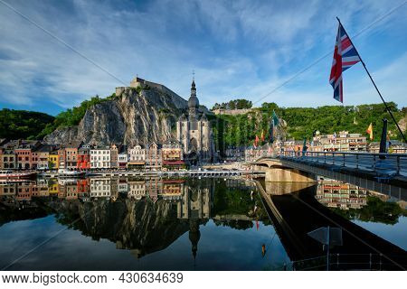 Picturesque Dinant town, Dinant Citadel and Collegiate Church of Notre Dame de Dinant and Pont Charles de Gaulle bridge over Meuse river with flag. Belgian province of Namur, Blegium
