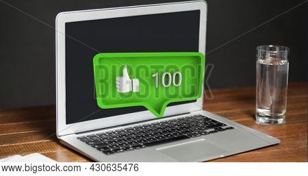 Digital composite of a glass of water beside a laptop on a wooden table with a yellow green message bubble with a like button and increasing numbers for social media