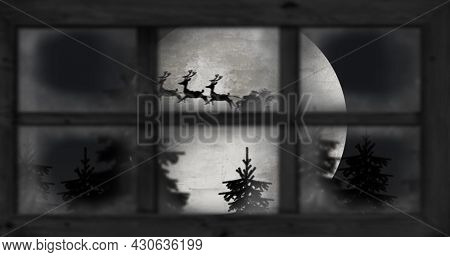 Image of silhouette of santa claus in sleigh being pulled by reindeer and winter christmas scenery with full moon seen through window. christmas festivity celebration concept digitally generated