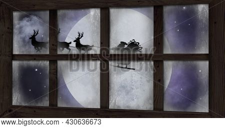 Image of silhouette of santa claus in sleigh being pulled by reindeer and winter christmas scenery with snow falling and full moon seen through window. christmas festivity celebration concept