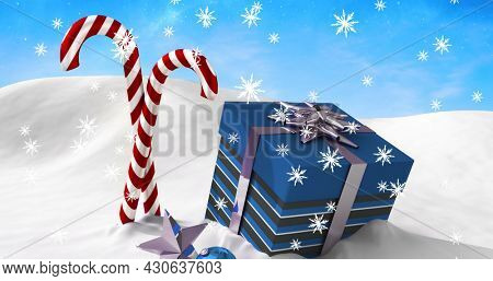 Image of two christmas candy canes and present over winter scenery seen through window. christmas festivity celebration concept digitally generated image.