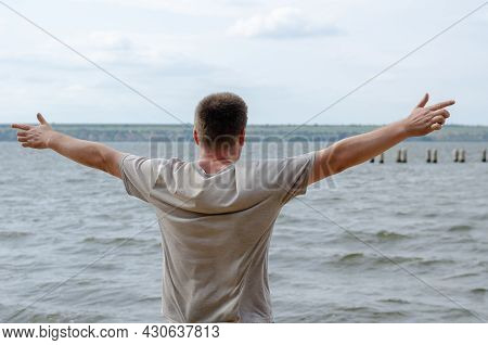 Half-length Portrait Of A Grown Man Standing On The Bank Of A Wide River. Man In A Gray T-shirt With