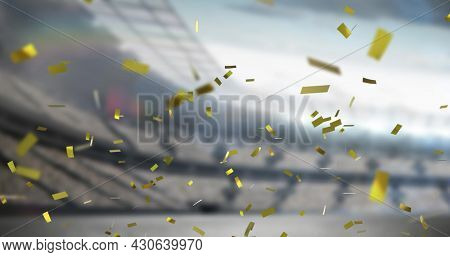 Image of golden confetti falling over empty sports stadium. competition victory celebration concept digitally generated image.