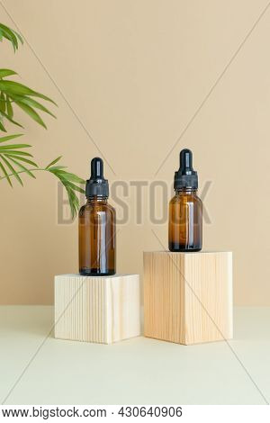 Containers With Lotion, Serum Or Essential Oil On A Wooden Podium On A Beige Background With Palm Le