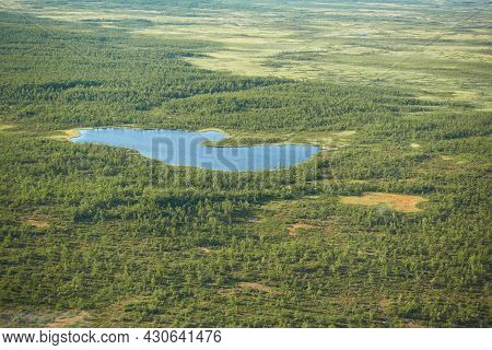 Aeriel View To Kiruna Wilderness From Helicopter With Small Lake Or Pond In The Middle Of The Swamps