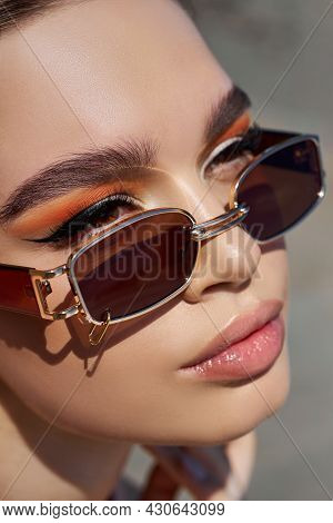 Portrait Of A Beautiful Woman With Bright Red Makeup And Dark Sunglasses Close-up. Red Shadows On Th