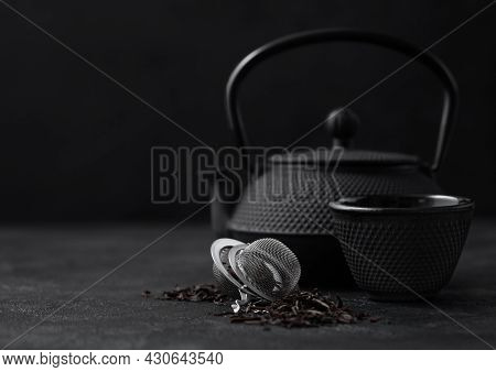 Black Loose Tea With Strainer Infuser And Iron Japanese Teapot And Cup On Dark Background.