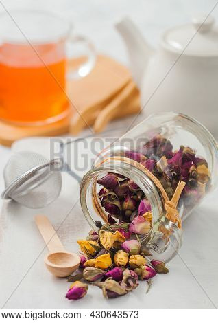 Rose Buds Mix Tea With Wooden Scoop And Strainer Infuser On White Background With Ceramic Teapot And