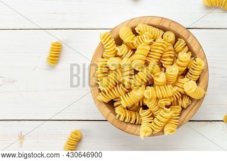 Raw Pasta Fusilli In Wooden Bowl On White Rustic Background. Space For Text.