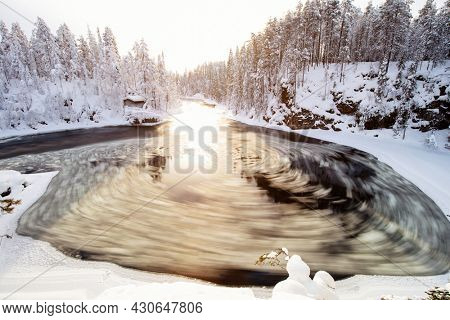 Stunning winter landscape view of snow covered hut by river in Oulanka National Park in Lapland Finland