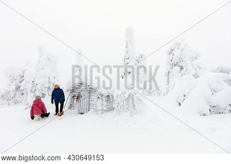 Family of father and daughter having rest break next to snow covered hut while hiking in beautiful winter forest in Lapland Finland