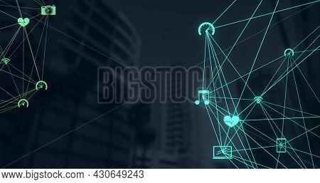 Digital composite image of Network of connection icons over tall buildings against black background. Global networking and business concept