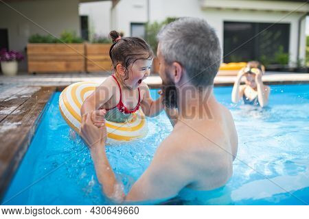 Father With Daughters Outdoors In The Backyard, Playing In Swimming Pool.