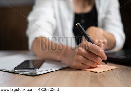 Business Lady Taking Notes While Working In The Office. Womans Hand With A Pen Close-up. The Manager