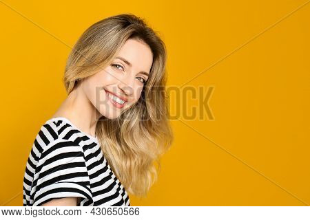 Portrait Of Happy Young Woman With Beautiful Blonde Hair And Charming Smile On Yellow Background. Sp