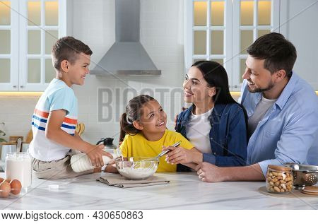 Happy Family Cooking Together At Table In Kitchen. Adoption Concept