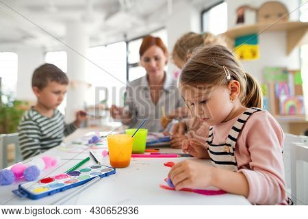 Group Of Small Nursery School Children With Teacher Indoors In Classroom, Painting.