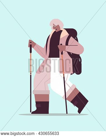 Senior Woman Hiker Traveling With Backpack And Sticks For Walk Nordic Walking Active Old Age