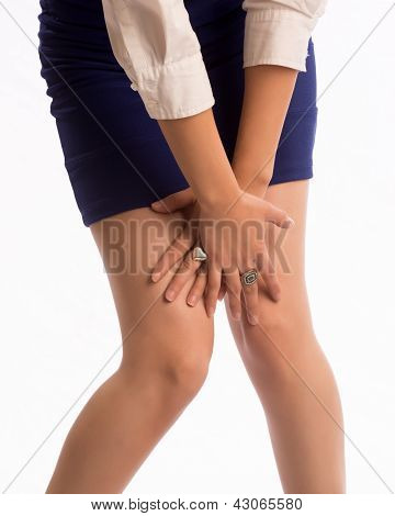 Woman in mini skirt covering her legs with her hands. poster