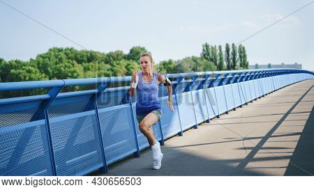 Mid Adult Woman Running Outdoors In City, Healthy Lifestyle Concept.