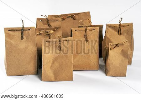 Some Craft Cardboard Pack Packages Tied With Raw Twine, Stand On White Background. Concept Of Ecolog