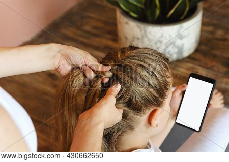 Young Blonde Girl Getting Her Long Hair Braided By Woman Hairdresser Before Sport Training While Loo