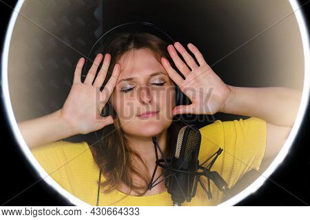 The Woman Sings At The Recording Studio With Her Hands Near Her Head. Happy Young Woman Singing A So