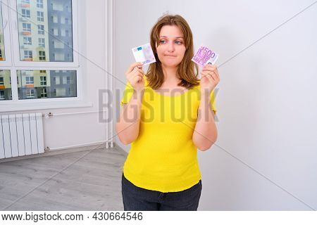 The Concept Of Wasted Money On Interest On The Loan. A Distraught Woman Holds A 500 Euro Bill Torn I