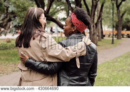 Back view of young cheerful and affectionate females interacting during walk in park