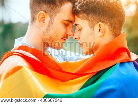 Gay couple with colourful LGBT flag enjoying nature outdoors, kissing and hugging. Young men family in love concept. Happiness