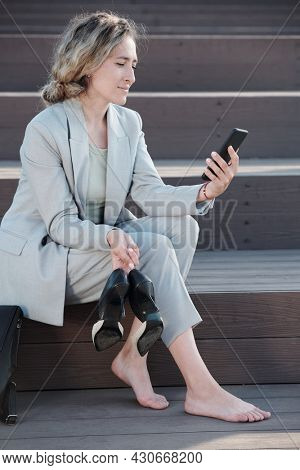 Young pretty businesswoman in suit holding her high-heeled shoes and smartphone