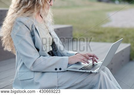 Young businesswoman in formalwear touching keys of laptop keypad outdoors