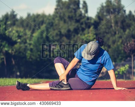 Female Runner Practise Yoga And Stretching Body From Back To Legs Cramp At The Stadium