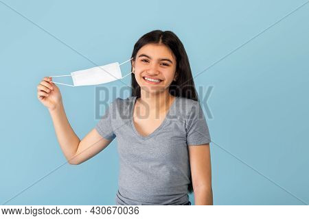 Free From Covid. Cheerful Indian Teen Girl Taking Off Face Mask And Smiling At Camera On Blue Studio
